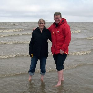 Two people in parkas standing barefoot in Arctic Ocean.