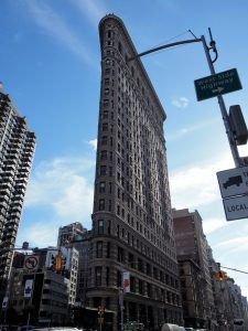 View of iconic Flatiron Building from street corner, with stree lights and signs in the way.