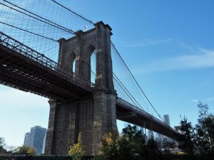 Shore-level view of Brooklyn Bridge tower and span to Manhattan