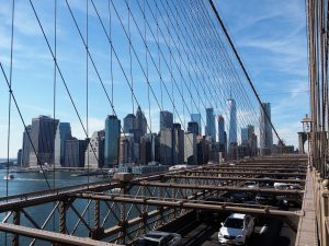 Bridge deck view of car deck, and Manhattan skyline through cables