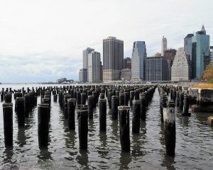 Posts in East River in foreground; Manhattan in background