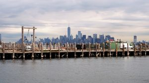 Working dock in foreground with Manhattan skyline on horizon