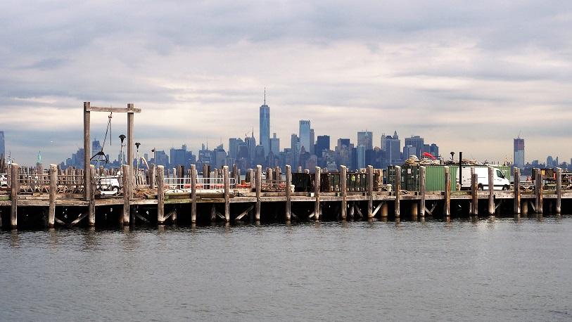 Working dock in foreground with Manhattan skyline on horizon