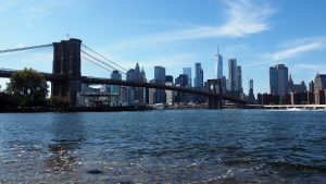East River, with Manhattan skyline showing through Brooklyn Bridge in background.