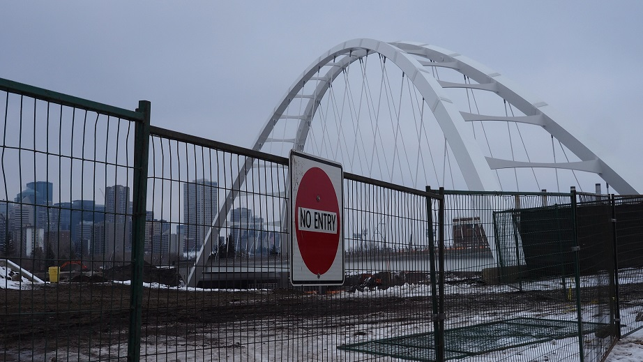 Construction fence with Walterdale Bridge in background.
