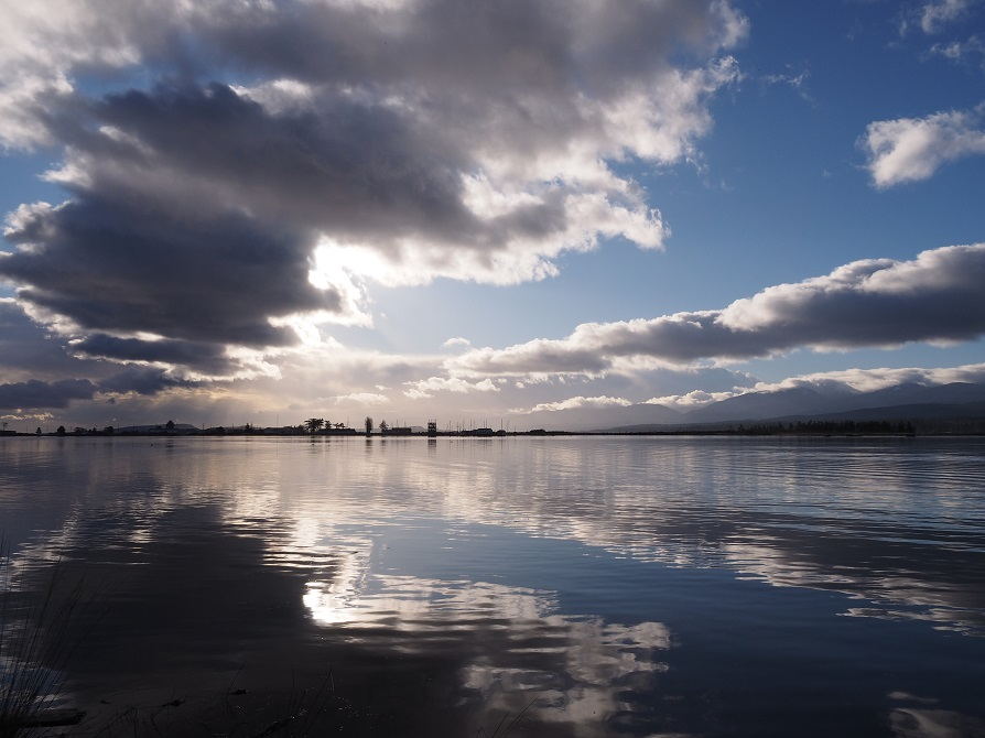 Dark and white clouds reflected in Comox Harbour in the early morning light.