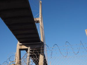 Vie of bridge from street level, with razor wire in foreground.