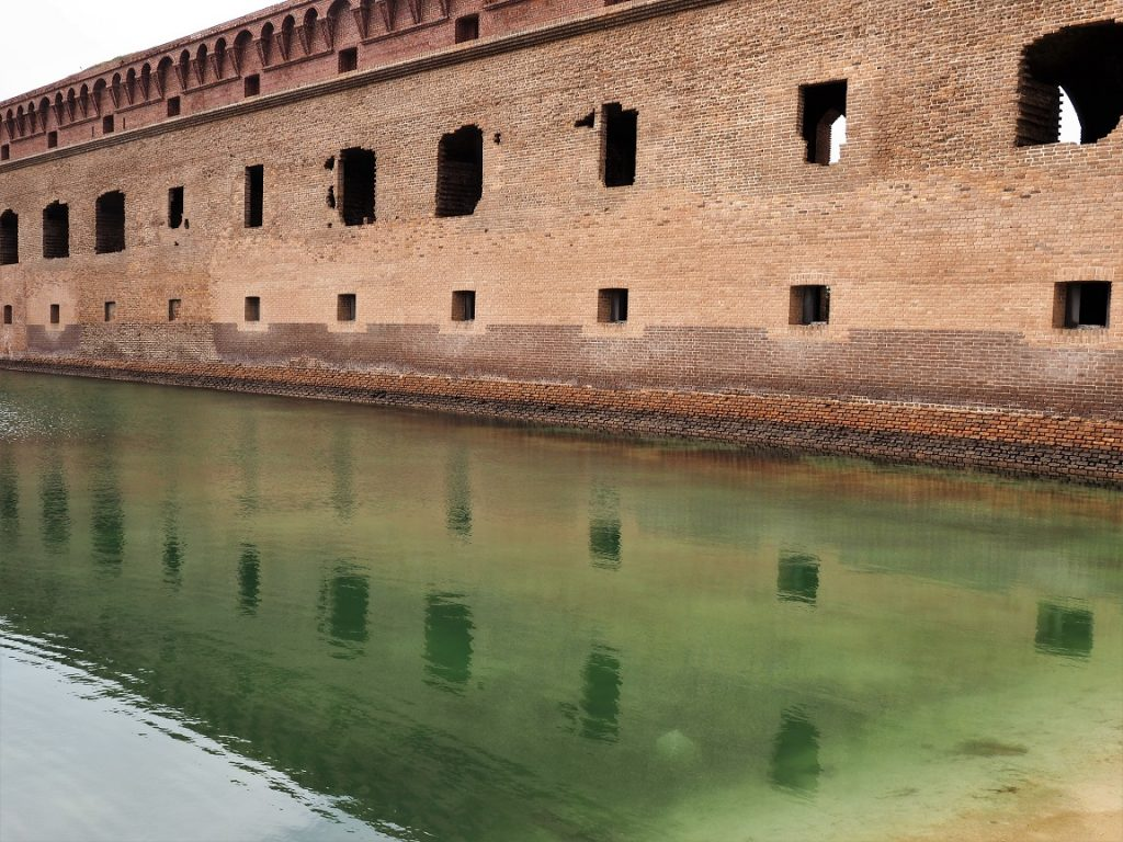 Wall of fort reflected in moat.