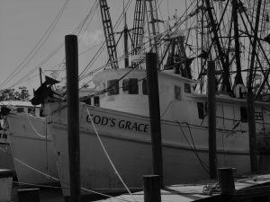 Black and white image of fishing boats tied up at dock.