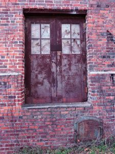 Old doors with broken window panes in abandoned warehouse