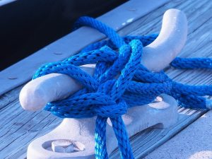 Blue nylon rope around cleat on pier
