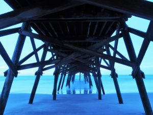 Surreal view of layers of blue - sand, water, sky - under wooden pier at dawn.