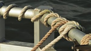 Tan and beige ropes tied off on boat railing
