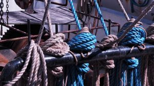 Blue and tan ropes on tied off on large black stanchion