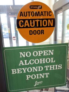 Grocery-store door sign advising patrons that they can't take open alcohol out into the parking lot