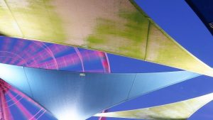 Moving Skywheel peeking through coloured, wing-shaped canvas awnings