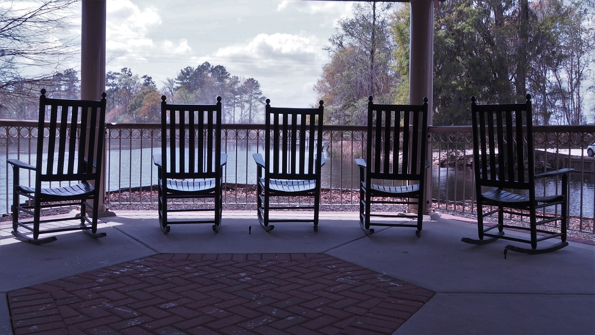 5 rocking chairs overlooking a river