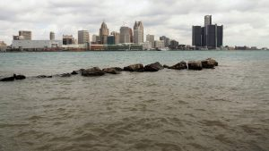 Shore-level view of Detroit River and city skyline at mid-day.