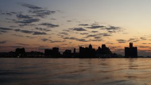 Detroit skyline in silhouette at sunrise.