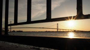 Ambassador Bridge at sunset, trhough railing along riverwalk