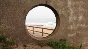 View through porthole in concrete beach shelter