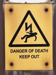 Graphic sign showing guy killed by electricity
