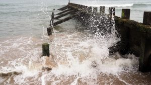Incoming tide splashing against breakwater