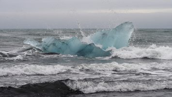 Blue iceberg in surf off black basalt beach