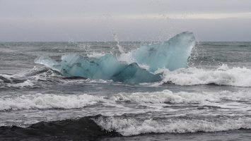 Blue iceberg in surf off black basalt beach