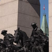 WWI soldiers on cenotaph, backed by Parliament Hill