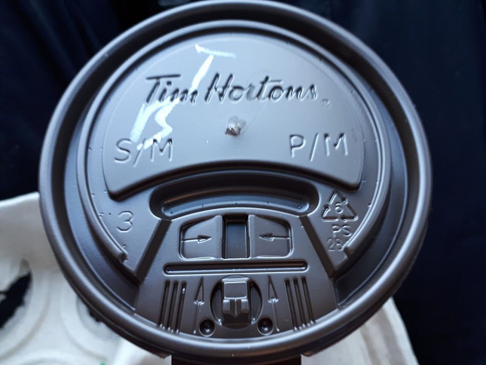 Face seen on lid from Tim Hortons coffee cup