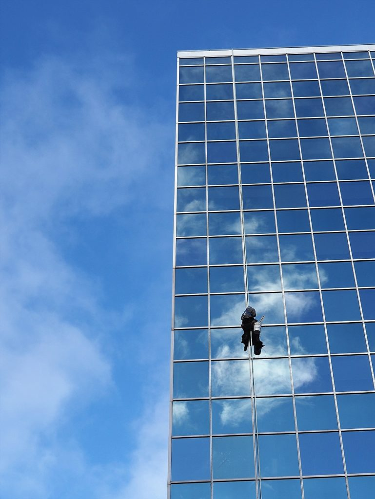Window washer/repairer hanging against high-rise