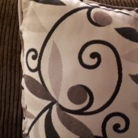 Face formed by curlicues on cushion