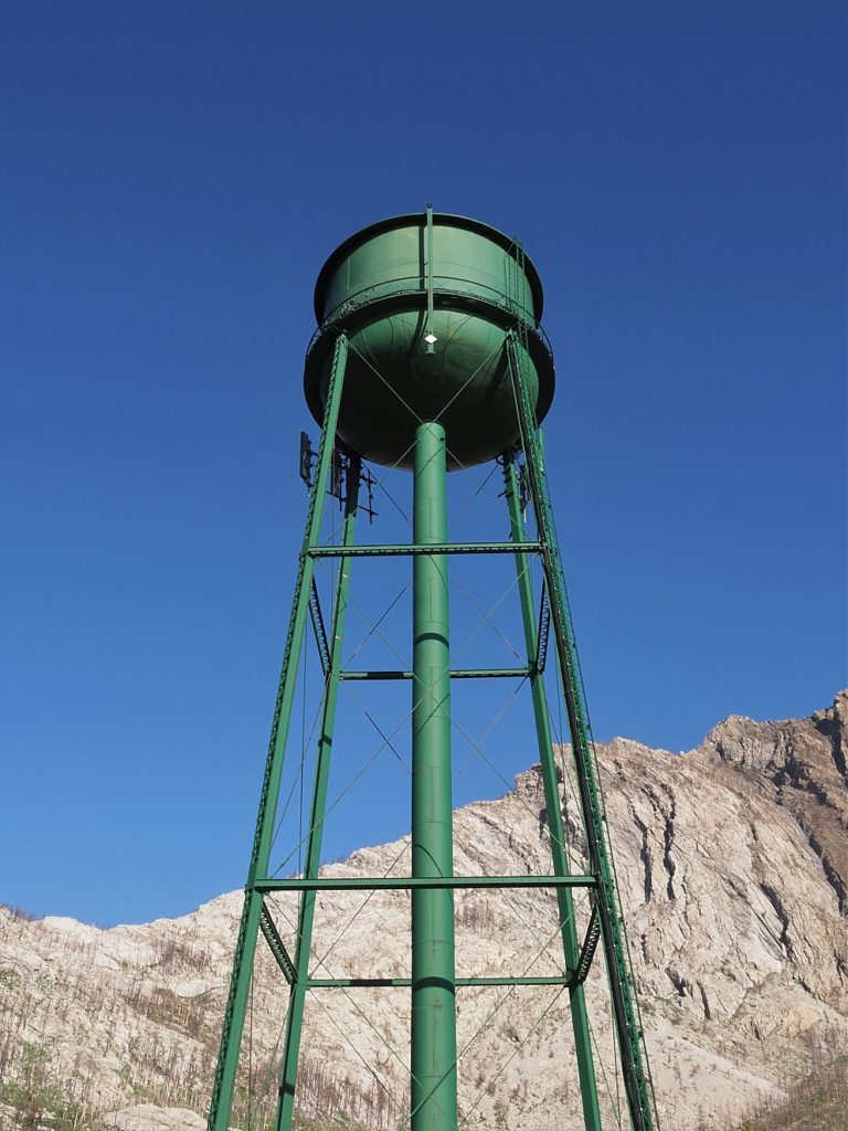 Water tower towering over mountain in background