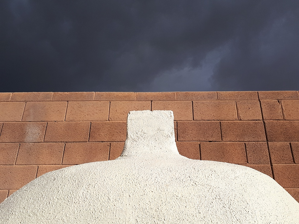 Fireplace, brick wall and storm clouds