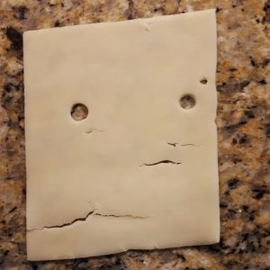 Accidental face in cheese slice